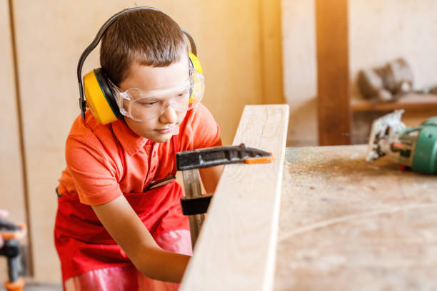boy in the workshop independently learns to work with wood in the carpentry workshop. The concept of a useful hobby in childhood and learning to work manually with hands stock photo