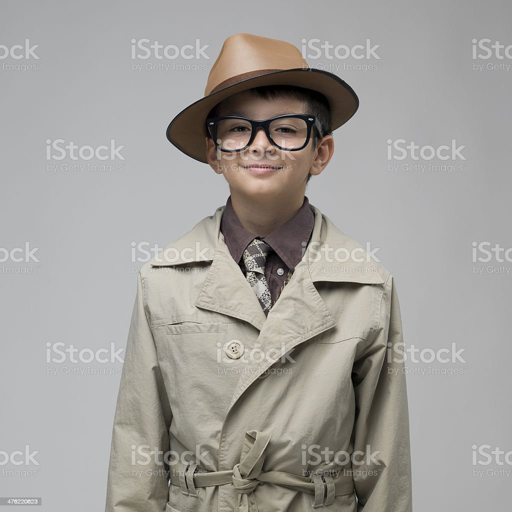 Boy in trench coat and glasses smiling on gray background. royalty-free stock photo