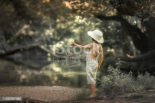 A boy in trousers and without shirts near rivers in the forest with wand in the hands of as if fisherman.