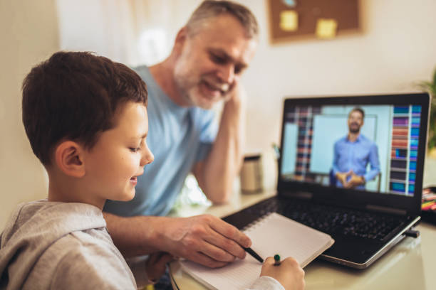 Boy in video conference with teacher on laptop at home. stock photo