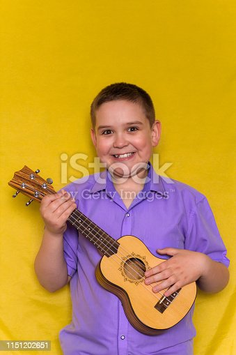 605742160 istock photo boy in violet shirt  plays on hawaiian guitar or ukulele iolated on yellow background 1151202651