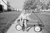 Little boy sitting in wagon in his front yard. 1957, Waterloo, Iowa, USA. Scanned film with grain.