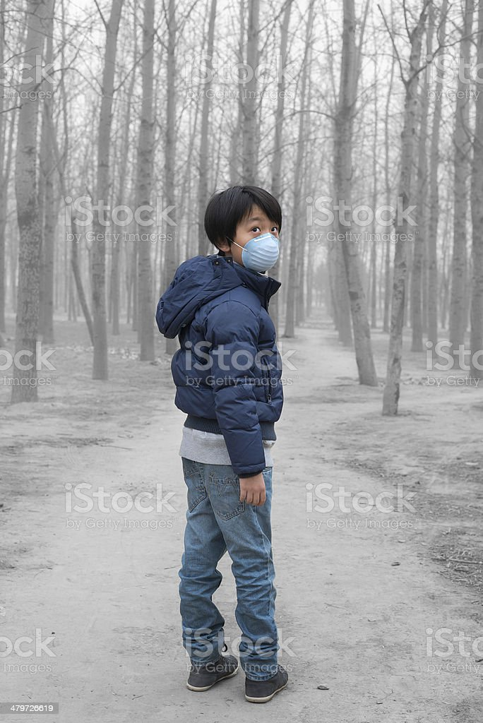 Boy in wearing mouth mask in front of dry forest stock photo