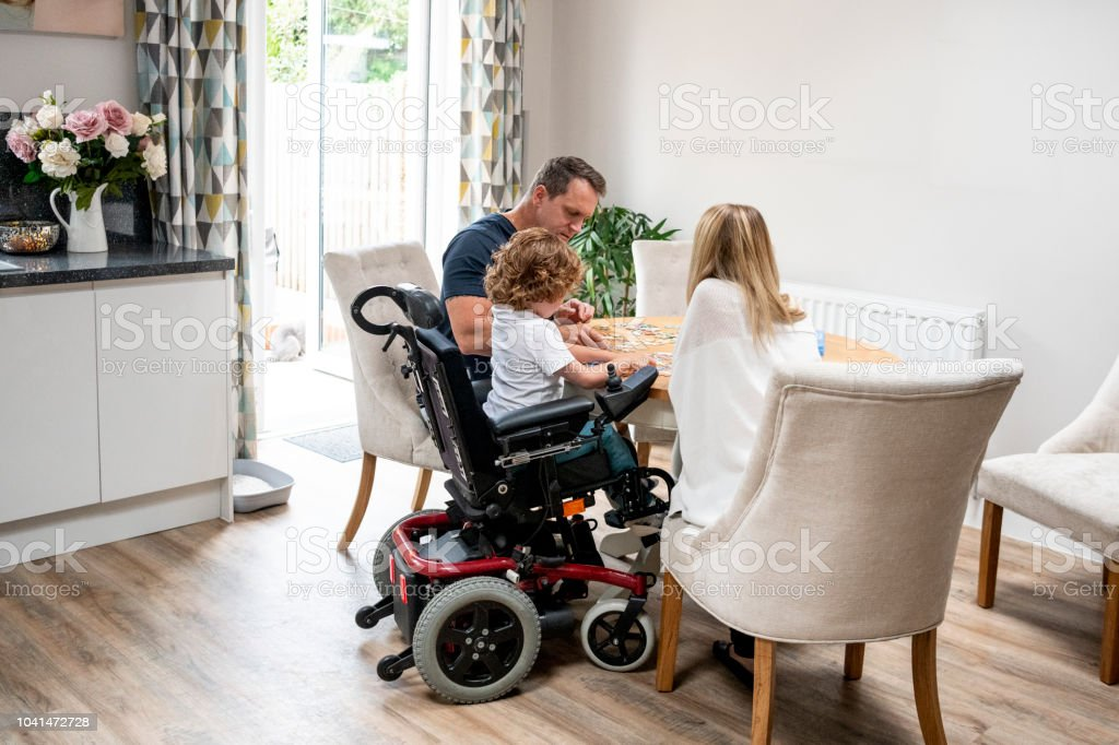 Boy in wheelchair doing jigsaw with parents stock photo