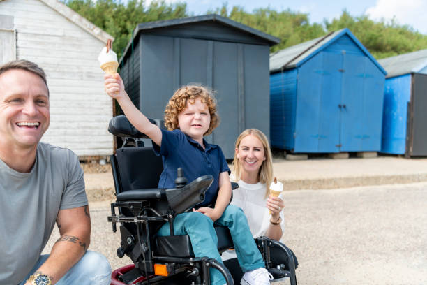 Boy in wheelchair holding up ice cream with parents, by beach huts stock photo