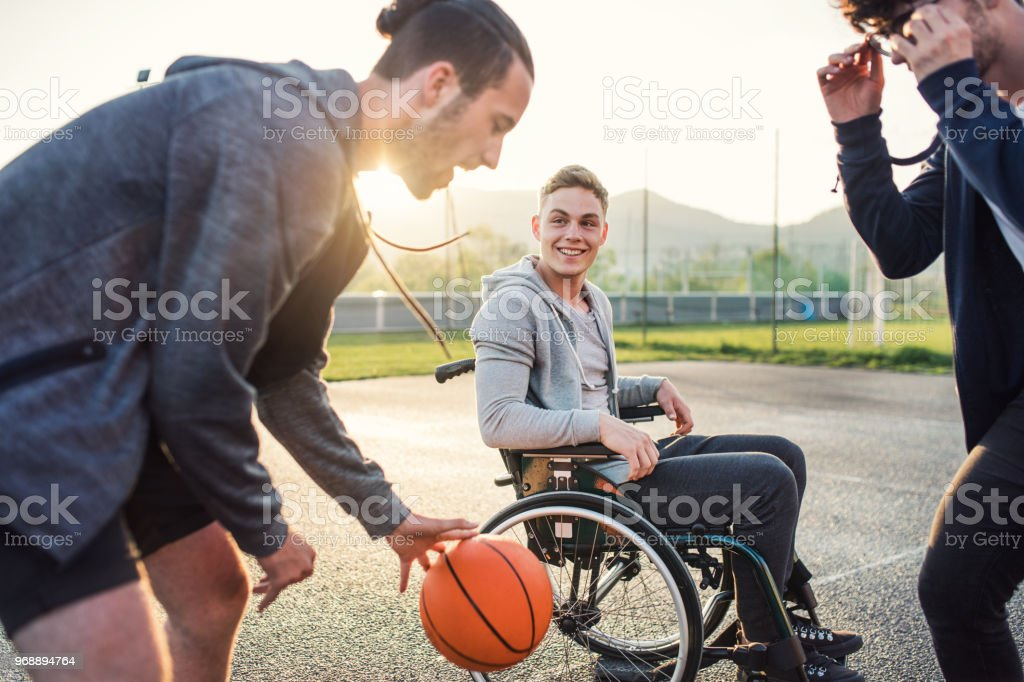 A boy in wheelchair with teenager friends outside playing basketball. Close up. stock photo