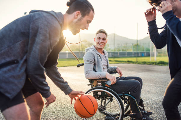 un garçon en fauteuil roulant avec des amis d'adolescent dehors jouer au basket-ball. bouchent. - sports en fauteuil roulant photos et images de collection