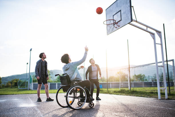 A boy in wheelchair with teenager friends outside playing basketball. stock photo