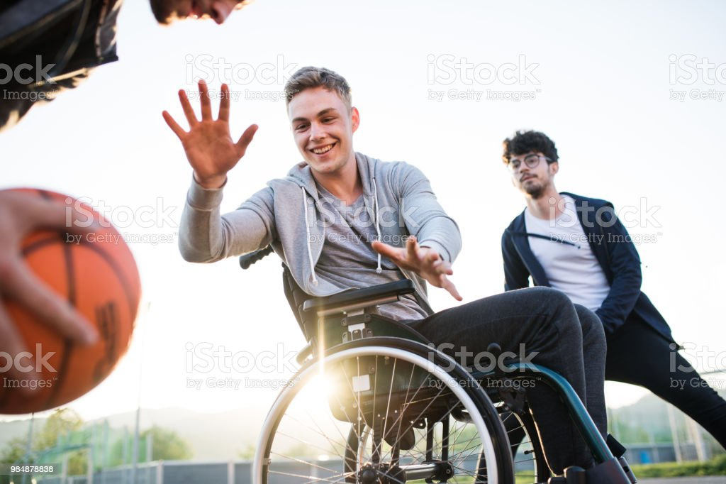 Um rapaz em cadeira de rodas com amigos de adolescente fora jogando basquete. - foto de acervo