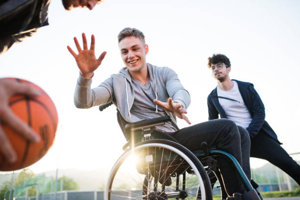 A boy in wheelchair with teenager friends outside playing basketball. A boy in wheelchair with two teenager friends playing basketball outside at sunset. leisure equipment stock pictures, royalty-free photos & images