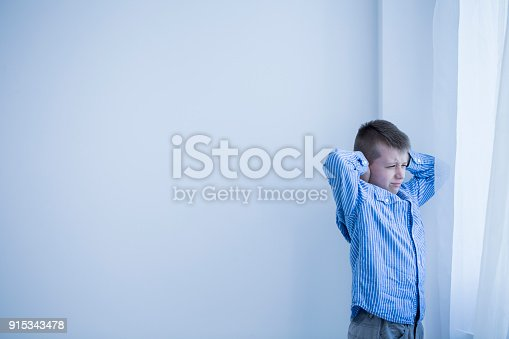 Young autistic, boy in a white, empty room standing next to a window covering his ears