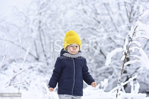 istock Boy in winter forest. Beautiful child on background of snowy trees, branches with snow. Cold and travel, winter tourism, active holidays in December, January and February. Adorable kid with cute face 1084727204
