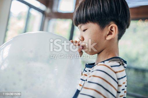 Boy inflates white balloon