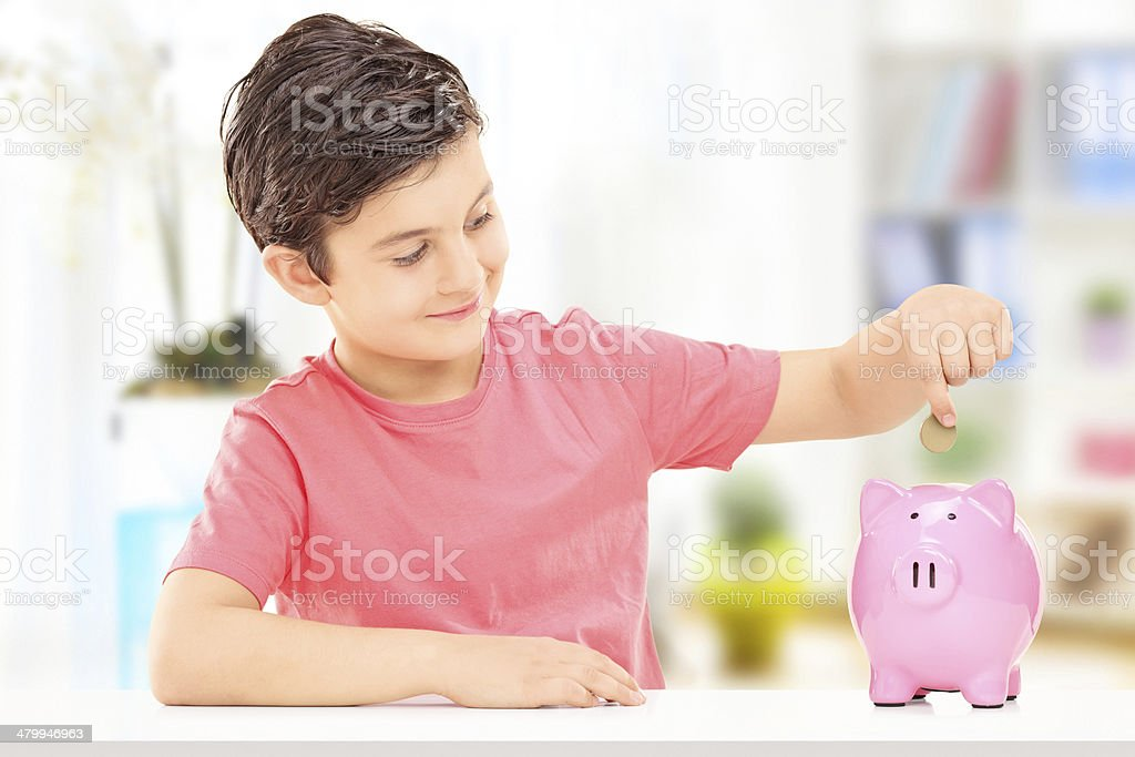 Boy inserting coins into a piggybank stock photo