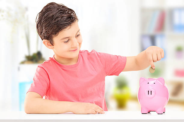 Boy inserting coins into a piggybank Boy inserting coins into a piggybank seated at table indoors allowance stock pictures, royalty-free photos & images