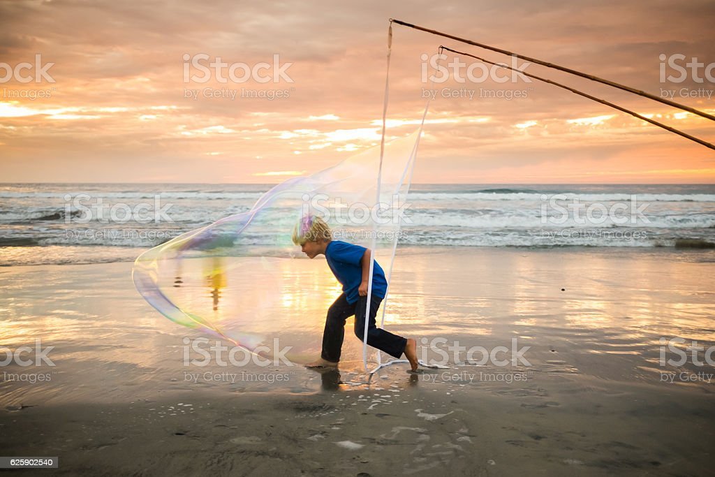 Boy Inside A Gaint Bubble On The Beach At Sunset stock photo