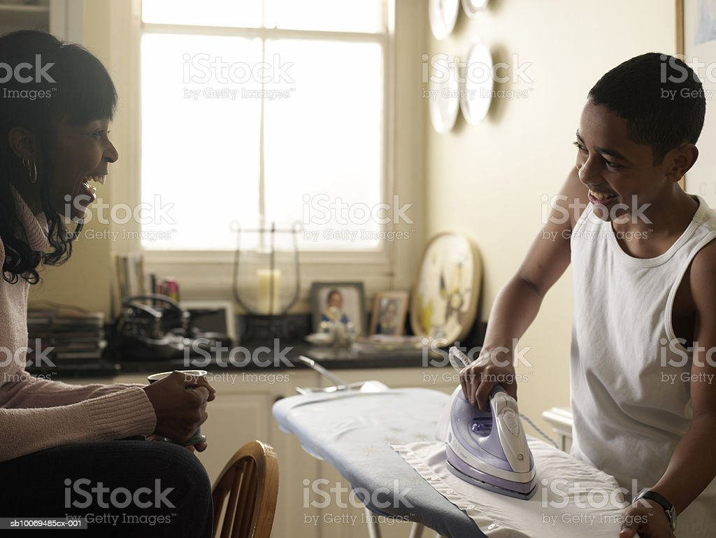 Boy (12-13) ironing shirt smiling to mother in kitchen royalty-free stock photo