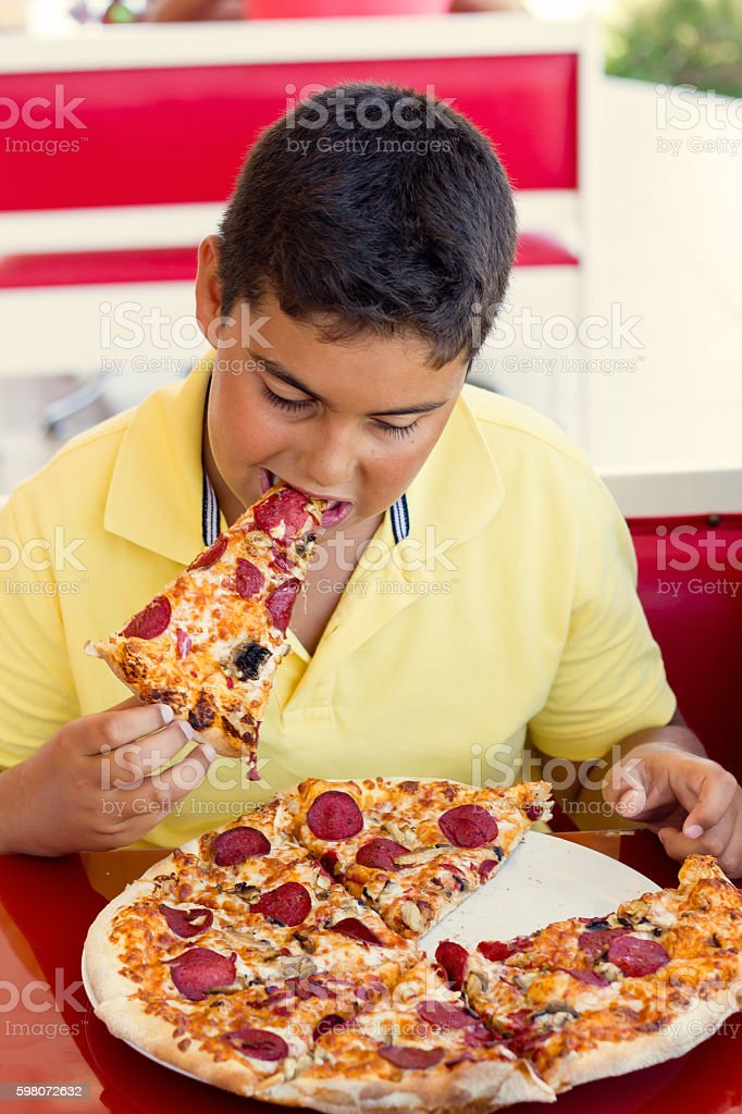 Boy Is Eating Pizza Slice stock photo