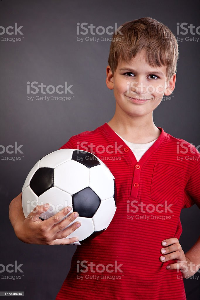 Boy is holding a soccer ball royalty-free stock photo