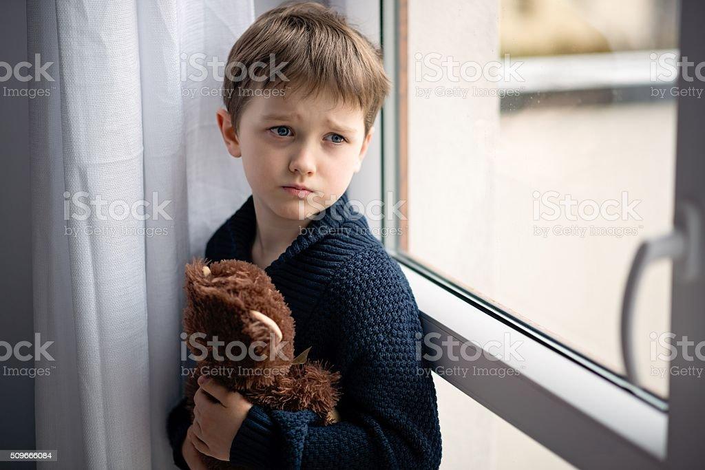 Мальчик, фигуру его плюшевого медвежонка. Стоя у окна. стоковое фото