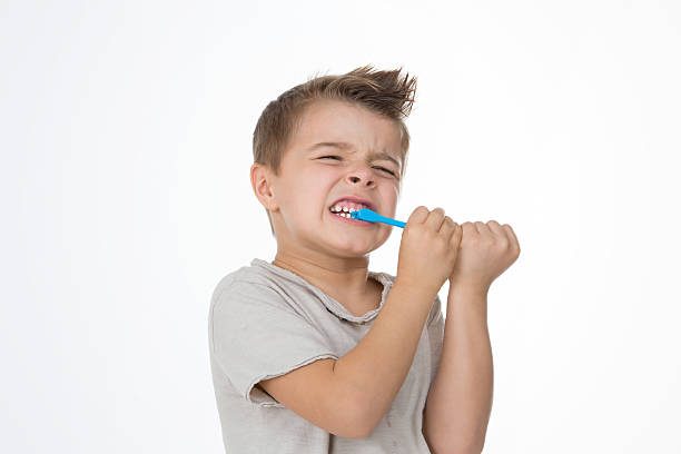 boy is hurting while cleaning teeth stock photo