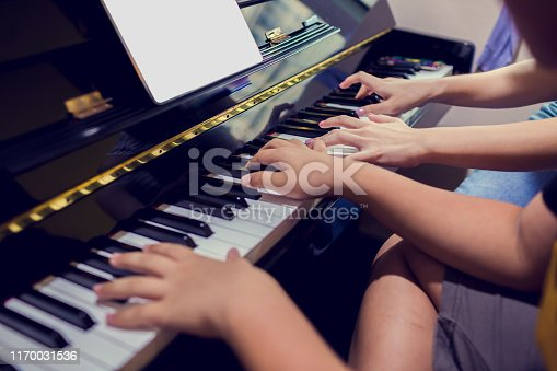 A boy is learning piano with woman teacher and music notation on tablet, four hands from two people playing piano, Musical instrument for learning music, The music learning concept, Selective focus.
