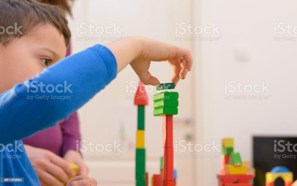 Junge spielt zu Hause mit Holzklötzen – Foto