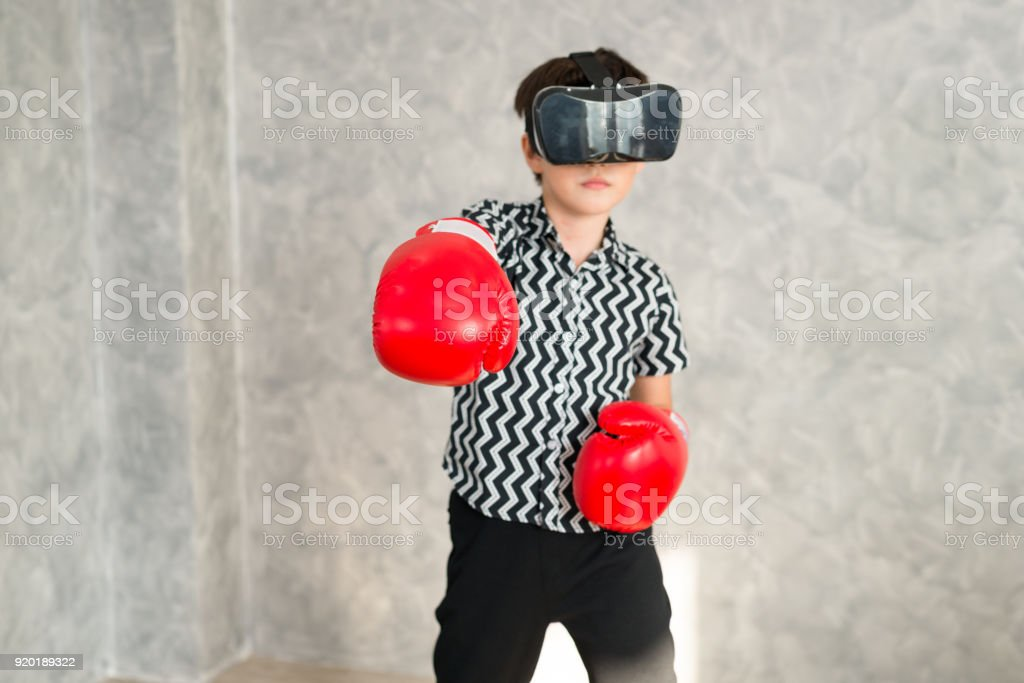 652cbb3e8801 A boy is playing boxing game with 3D virtual reality headset. - Stock image  .