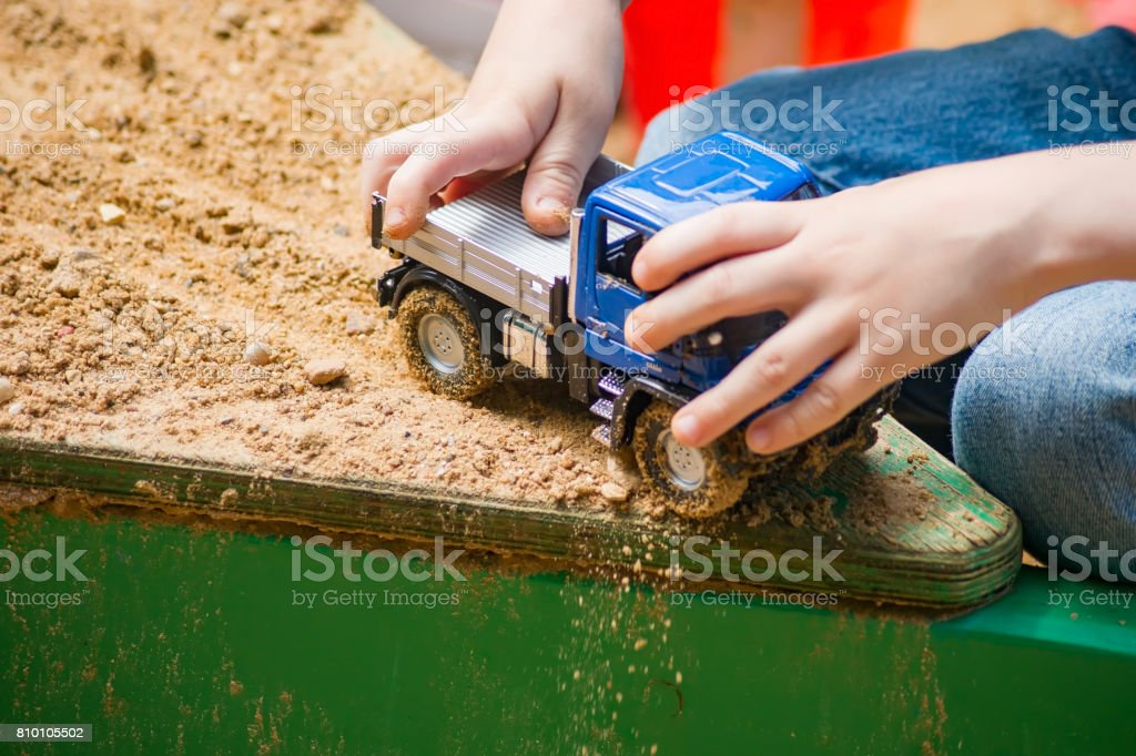 A boy is playing in a truck in a sandbox stock photo