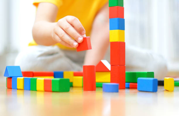 Boy is playing on the floor with wooden blocks . stock photo