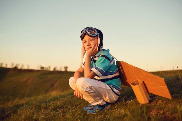 Junge spielt mit einem Flugzeug über die Natur bei Sonnenuntergang – Foto