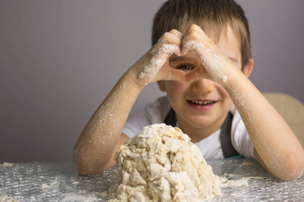 Boy is prepearing pizza dough stock photo