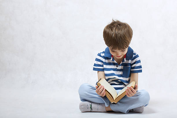 Boy is reading a book on a white background stock photo