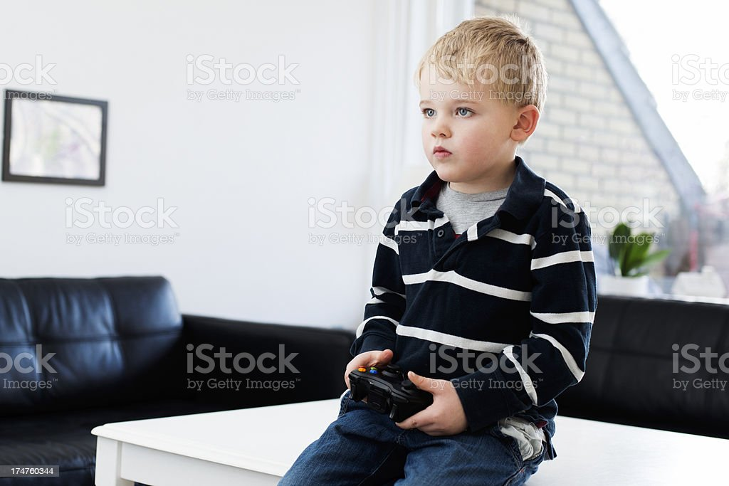 Boy is really focused on playing video game royalty-free stock photo