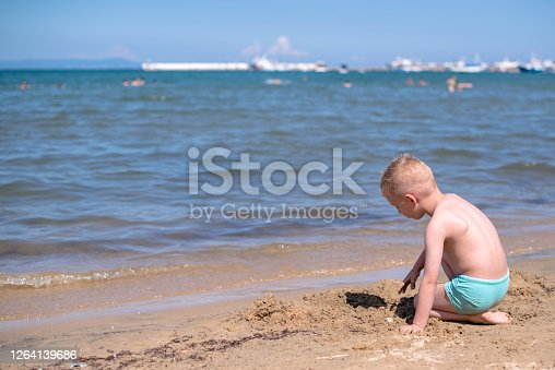 Boy is sitting on a beach and playing in sand