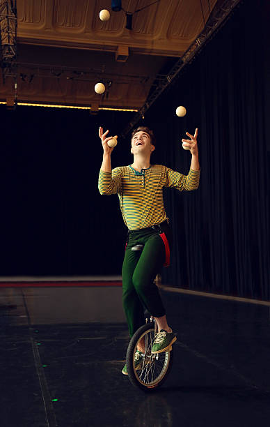 boy juggling and riding unicycle - circus stok fotoğraflar ve resimler