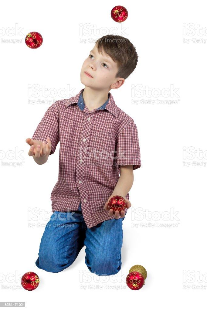 Boy juggling with Christmas tree balls. stock photo