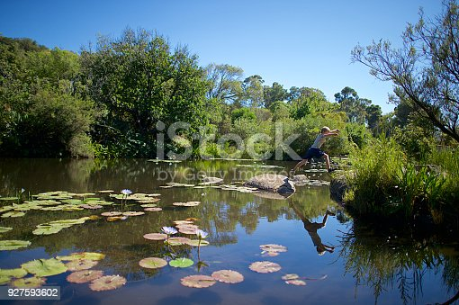 509813720 istock photo Boy jumping back over water with reflection 927593602