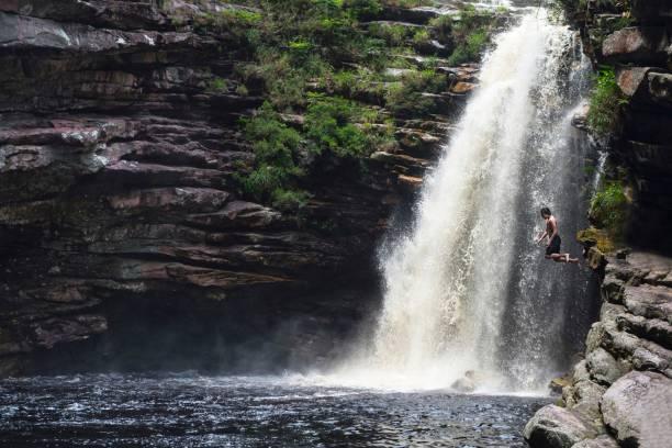 Junge in einem Wasserfall springen – Foto