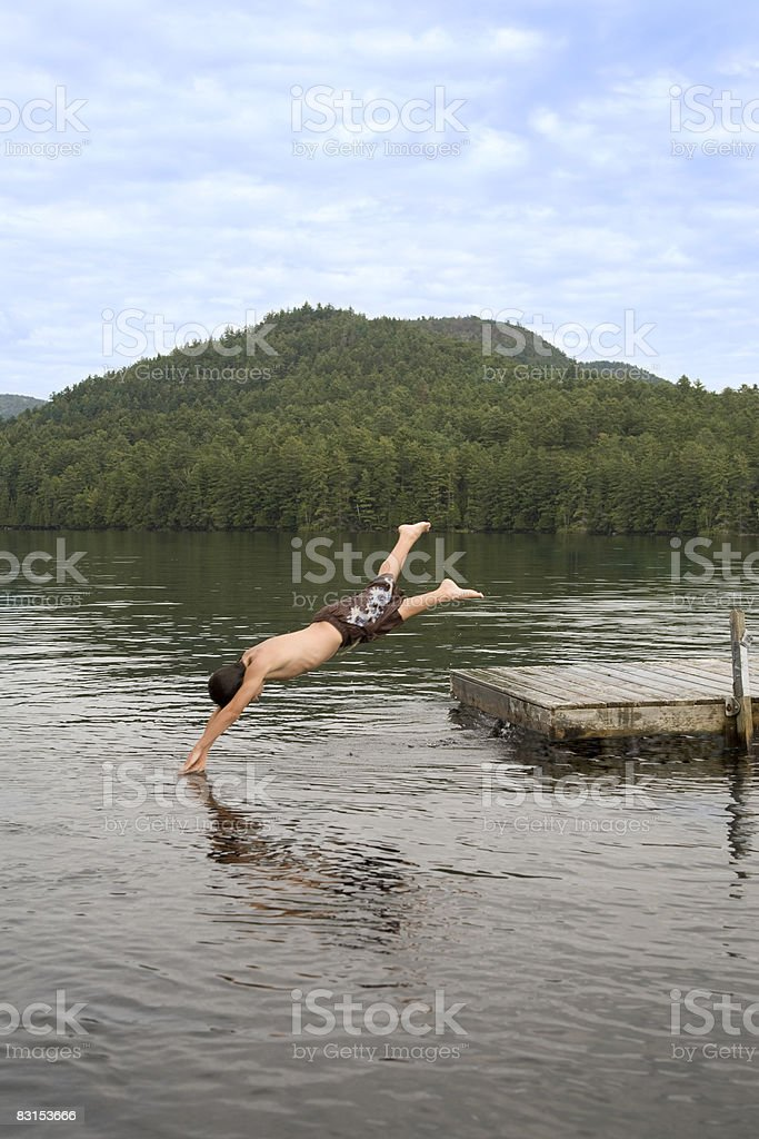boy jumping in lake zbiór zdjęć royalty-free