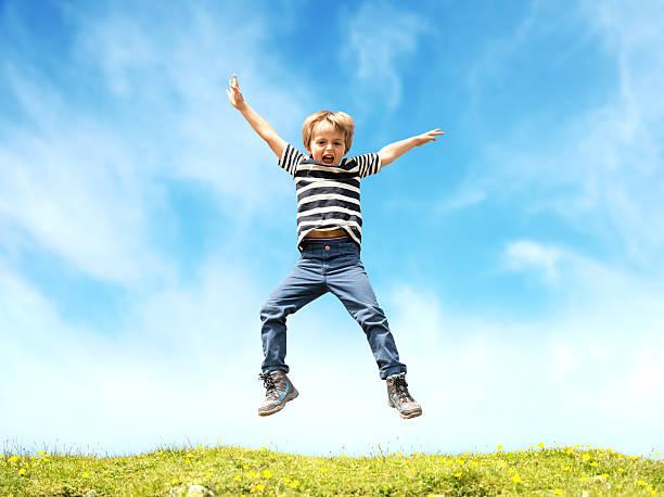Niño saltar en prado - foto de stock