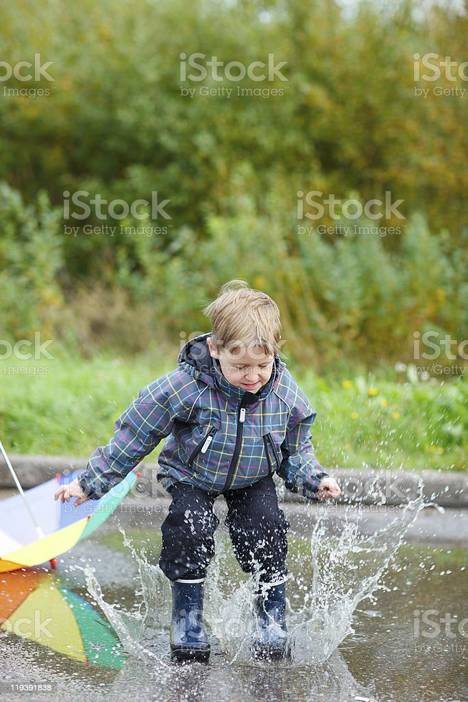 Boy jumping in puddle stock photo