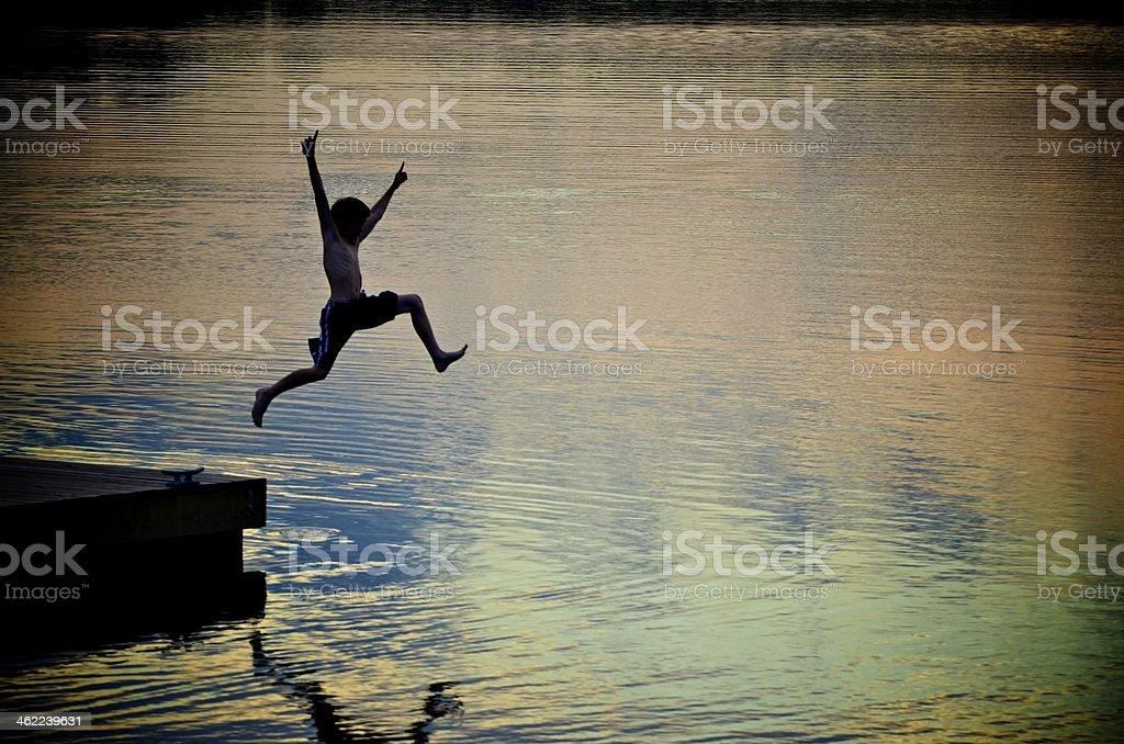 Boy Jumping Into Lake at Sunset stock photo