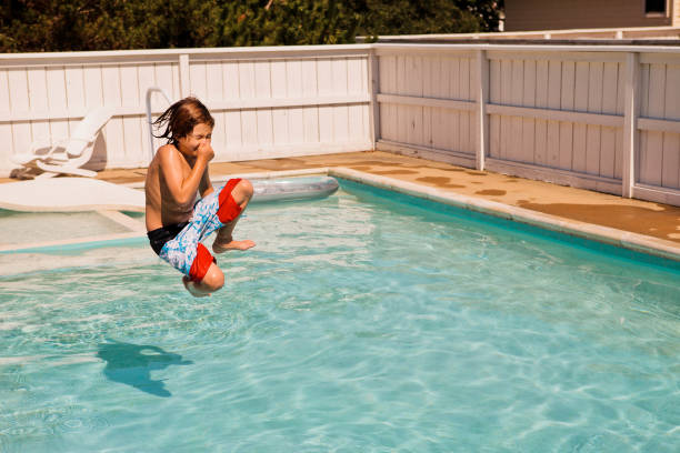 boy jumping into pool young boy jumping into a swimming pool taking the plunge stock pictures, royalty-free photos & images