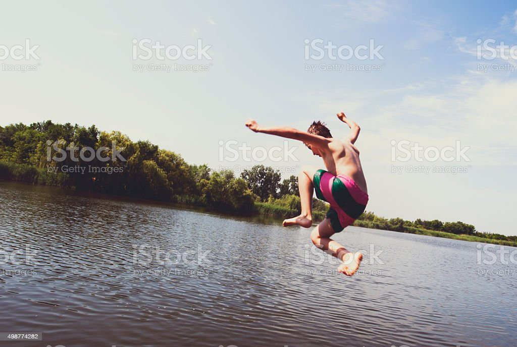 Boy jumping into the river stock photo