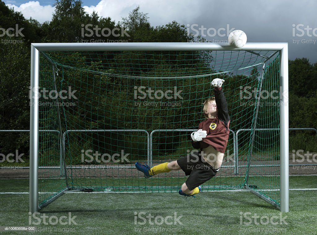 Boy (8-9 years) jumping mid air catching ball at goal post royalty-free 스톡 사진
