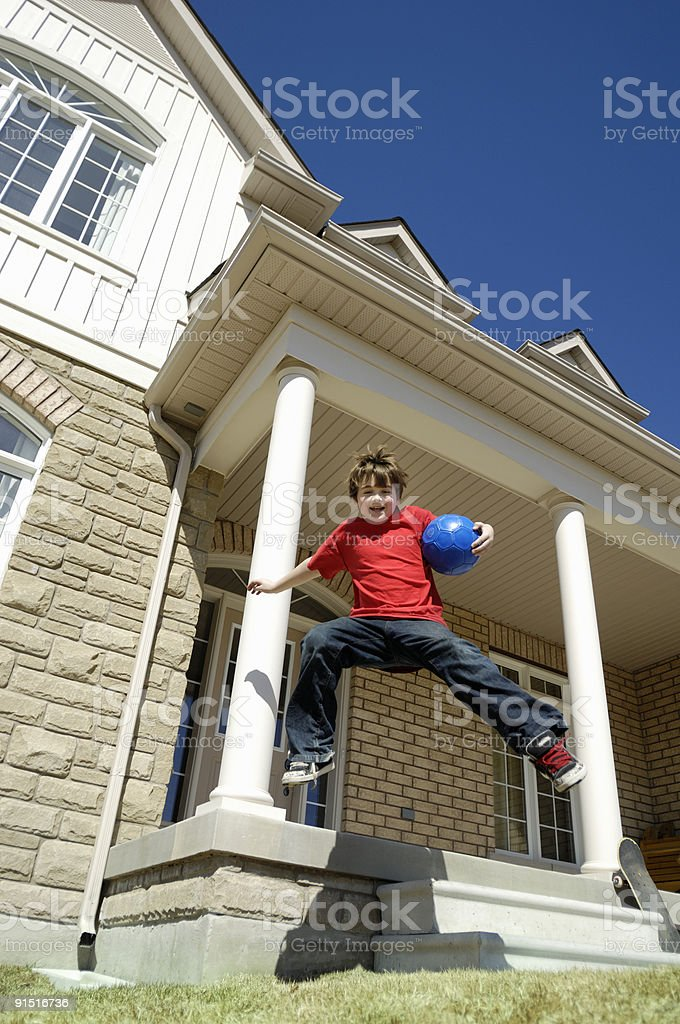 Boy jumping off porch stock photo
