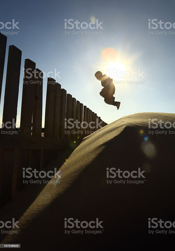 Boy Jumping Off Sand Dune stock photo