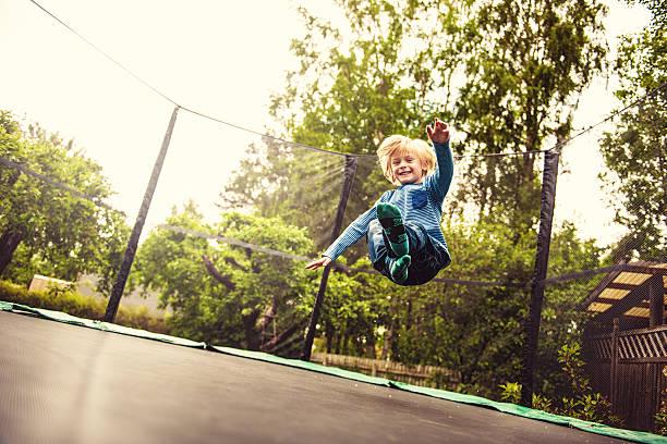 niño saltar en un trampolín - trampolín artículos deportivos fotografías e imágenes de stock