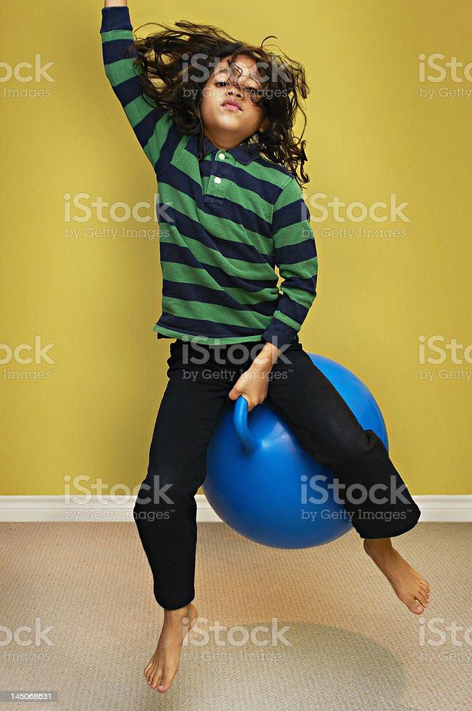 Boy jumping on bouncy ball stock photo